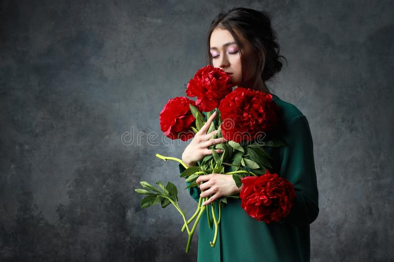 People and international women`s day concept - happy asian young woman with bunch of peony flowers over grey background royalty free stock photo