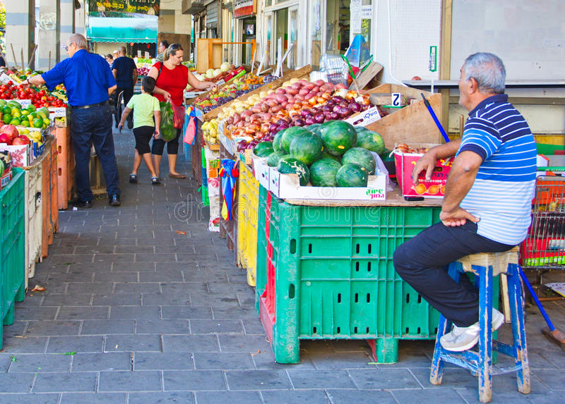 People on an Israel outdoor fruit and vegetable market. TEL AVIV - OCT 3, 2014: People shopping for fresh produce in a traditional Tel Aviv outdoor fruit and stock images