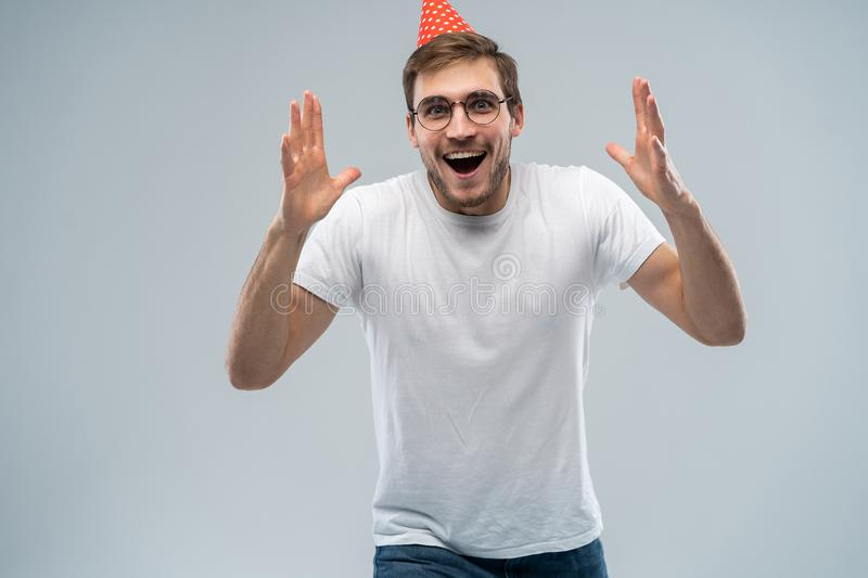 People, joy, birthday, anniversary, fun and party concept. Picture of handsome astonished young man with cone hat on his. Head celebrating birthday among stock images