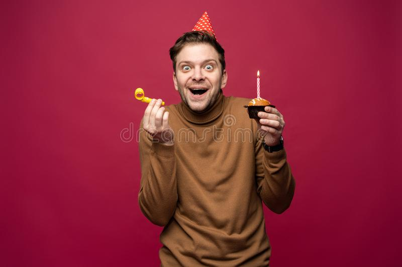 People, joy, fun and happiness concept. Relaxed happy birthday guy looking cheerful, smiling happily, posing for picture. Holding cupcake royalty free stock images