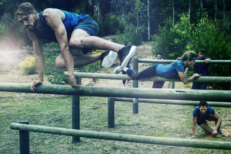 People jumping over the hurdles during obstacle course. In boot camp stock images