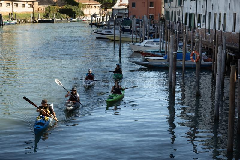 People kayaking in the Venetian canal. Venice, Italy. Group of people kayaking in the Venetian canals. Venice, Italy stock image