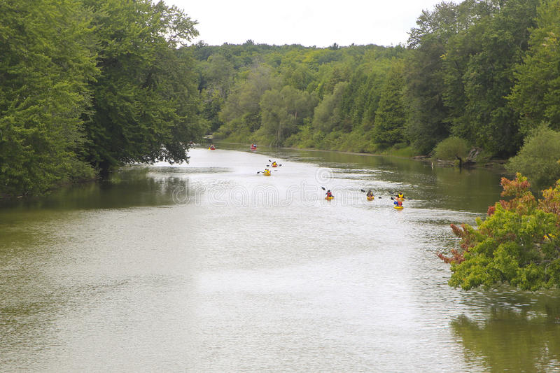 People in kayaks and canoes, Nottawasaga River, Midland, Ontario, Canada. People in kayaks and canoes on Nottawasaga River in Midland, Ontario, Canada on sunny stock image
