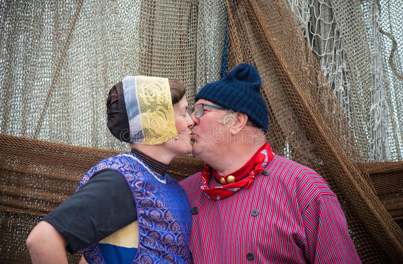 People kissing each other. URK, NETHERLANDS - MAY 19, 2018: Unknown couple in traditional costumes kissing each other on the Urkerdays. Urk is on of the best stock photography