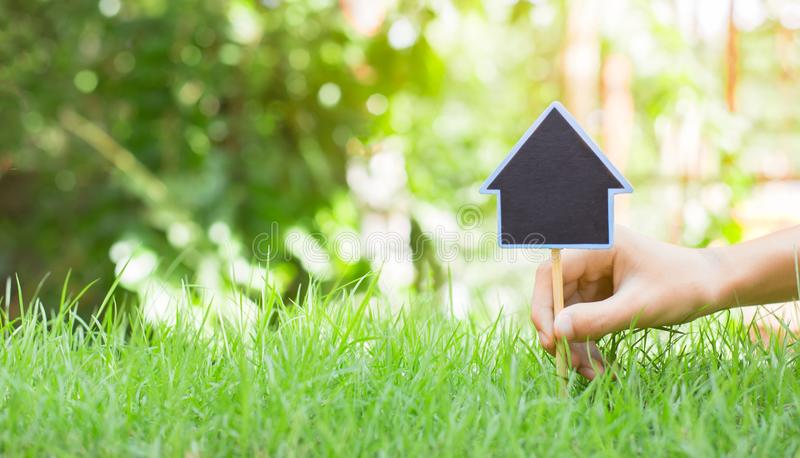 People are lacing House symbol with location pin and green grass in real estate sale or property investment concept, planning royalty free stock photography