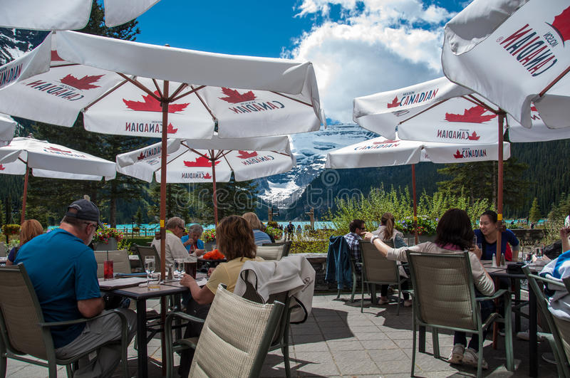People on Lake Louise patio. People admiring Lake Louise on a hotel patio on a warm summer day royalty free stock photos
