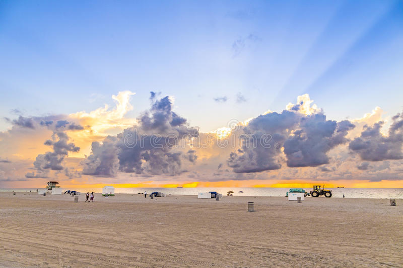 people in late afternoon walk along south beach and enjoy the sunset royalty free stock photo