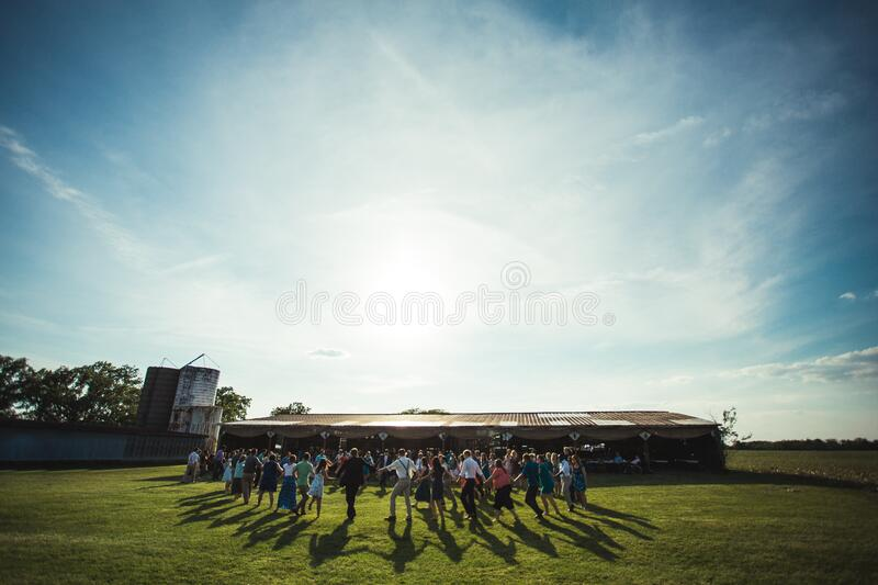 People on the Lawn Grass Running to the House during Daytime royalty free stock images