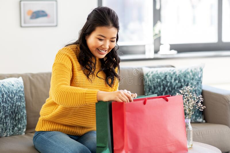 Asian young woman with shopping bag at home. People and leisure concept - happy smiling asian young woman in yellow sweater with shopping bag sitting on sofa at royalty free stock image