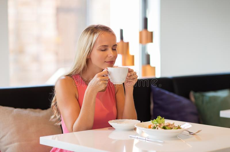 Woman eating and drinking coffee at restaurant royalty free stock images