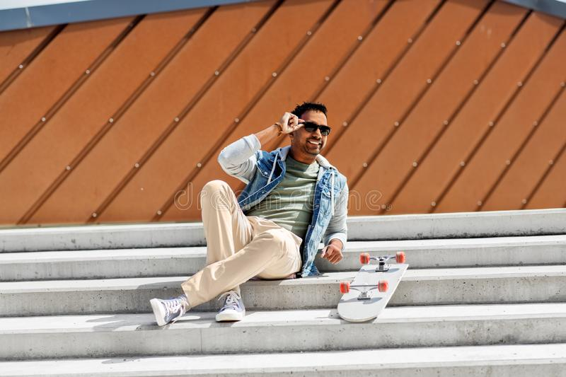 Indian man with skateboard sitting on city stairs. People and leisure concept - smiling indian man with skateboard sitting on stairs in city royalty free stock images