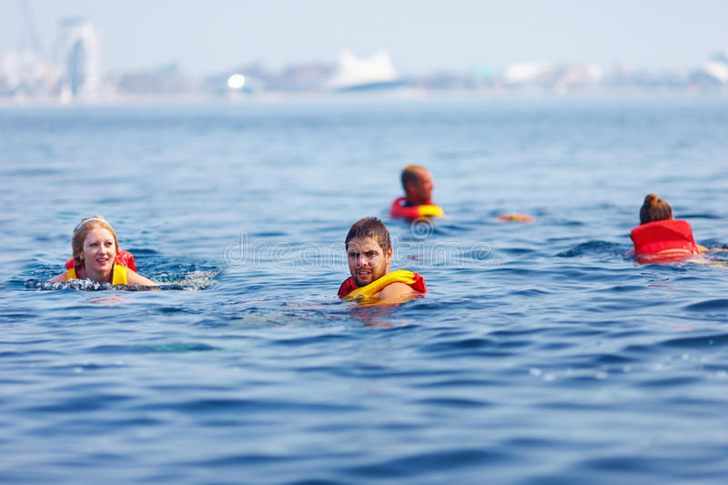 People in lifejackets swimming in open sea. People in life jackets swimming in the open sea stock photos