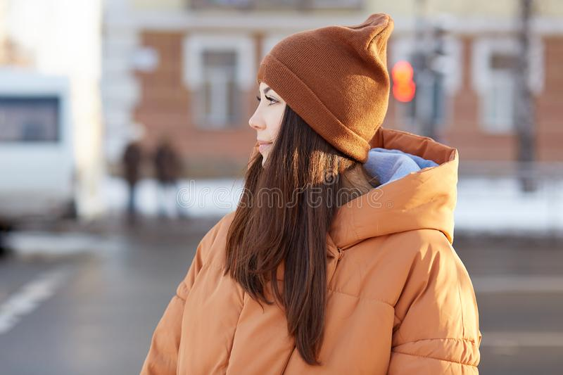 People, lifestyle concept. Brunette pretty European woman wears brown stylish hat and jacket, poses against blurred city stock image