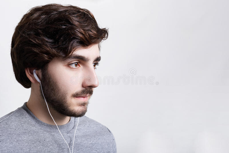 People and lifestyle concept. Sideways portrait of handsome young bearded man wearing grey sweater listening to music on white ear royalty free stock photography