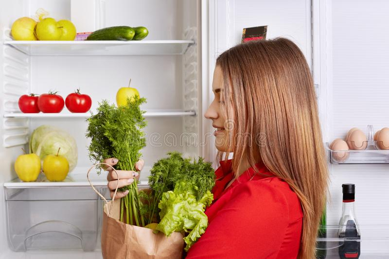 People, lifestyle and healthy eating concept. Sideways shot of adorable woman holds paper box with dill and lettuce, has fridge fu stock photo