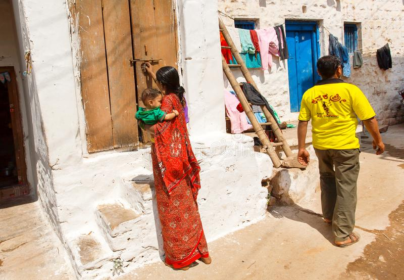 People living in poor small houses of narrow street of traditional town in Karnataka state. BADAMI, INDIA - FEB 8: People living in poor small houses of narrow royalty free stock images