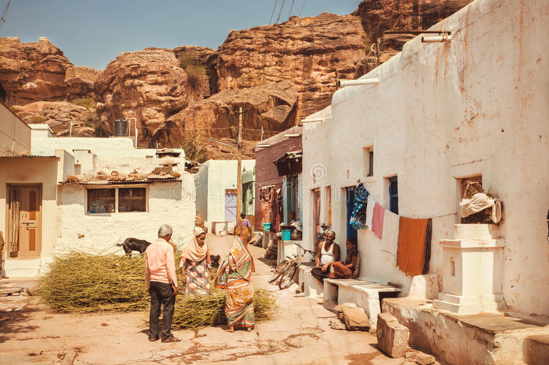 People living in small village houses on narrow street of traditional town. BADAMI, INDIA - FEB 8: People living in small village houses on narrow street of royalty free stock images