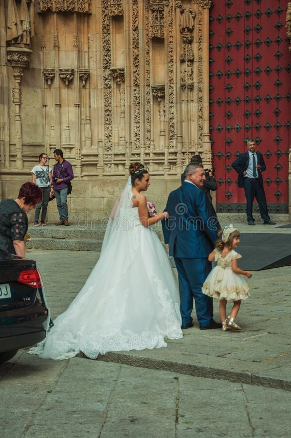 People looking at bride in front the New Cathedral at Salamanca. Salamanca, Spain - July 21, 2018. People looking at bride enter through the door of the New royalty free stock photography