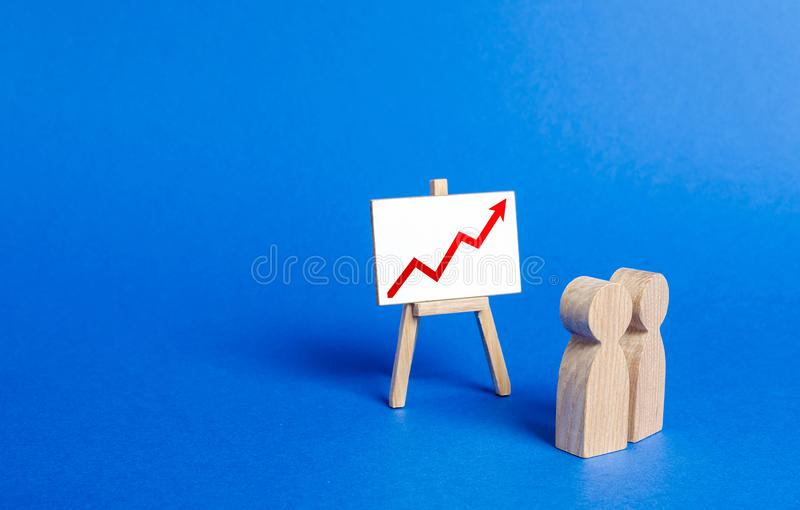 People looking at the easel stand with red arrow up positive trend. Analytics and processing of financial economic data indicators stock photography