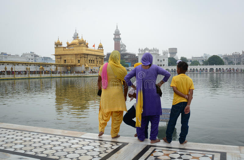 People looking at the Golden temple with the lake in Amritsar, India royalty free stock images