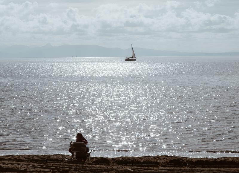 People looking the horizon over a calm sea with sail boat and blue cloudy sunny sky - peace relax concept.  stock image
