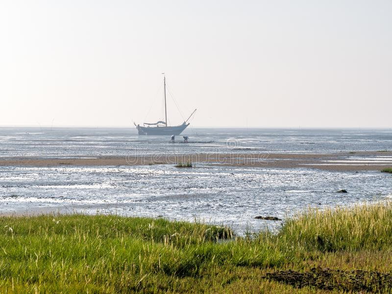People looking for shellfish in mudflats and dried out sailboat at low tide, Waddensea near Schiermonnikoog, Netherlands royalty free stock photography