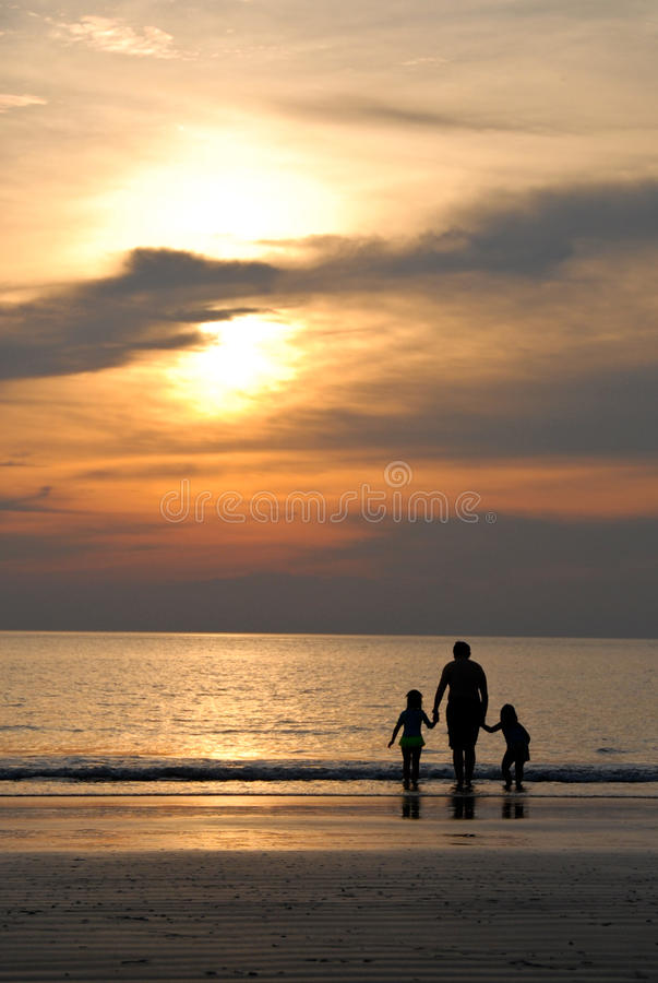 People looking at Sunset by beach. A family looking at the sunset by the beach stock photography