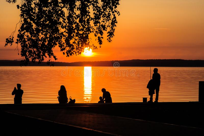People looking at the sunset or the sunrise on the lake royalty free stock photo