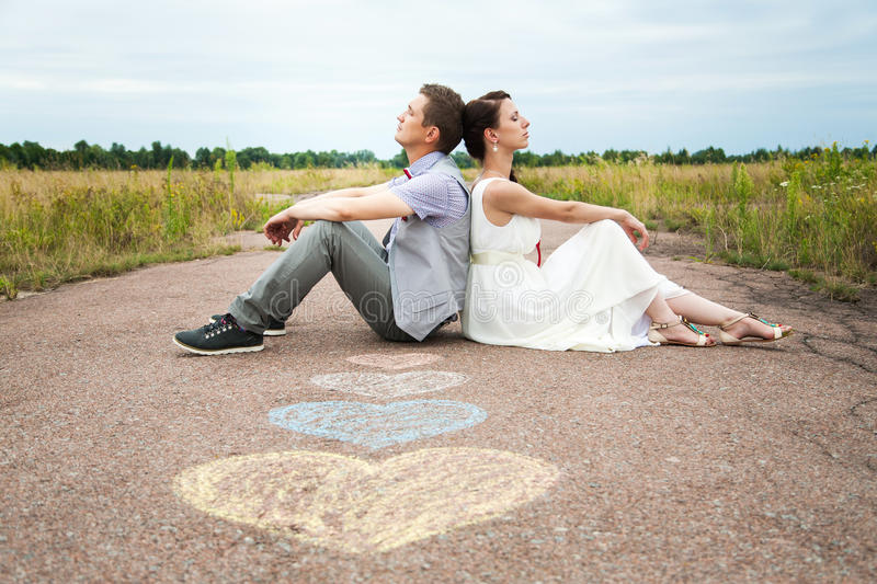 People in love. Wedding couple sitting on ground. love symbols on pavemant . hearts. people in love. happy bride and groom portraits. men and women sitting back royalty free stock images