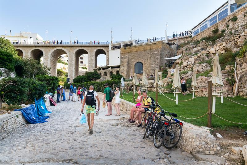 People on lovely beach Lama Monachile, Polignano a Mare, Italy. POLIGNANO A MARE, ITALY - JULY 6 2018: People on lovely beach Lama Monachile, Adriatic Sea royalty free stock image