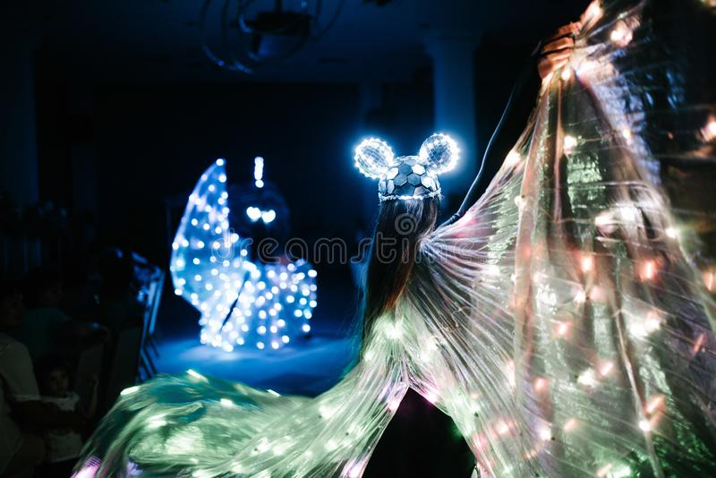 People in glowing costumes dancing in the dark. People in luminous costumes dance in the dark for a holiday, event, dancing, entertainment, dancer, light, glow royalty free stock image