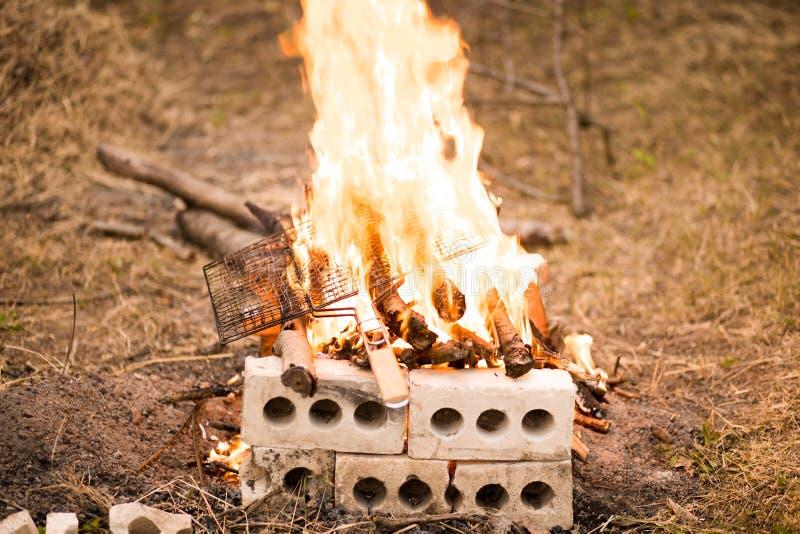 People make fire wood outdoor in garden. People make fire wood outdoor in summer garden royalty free stock photos