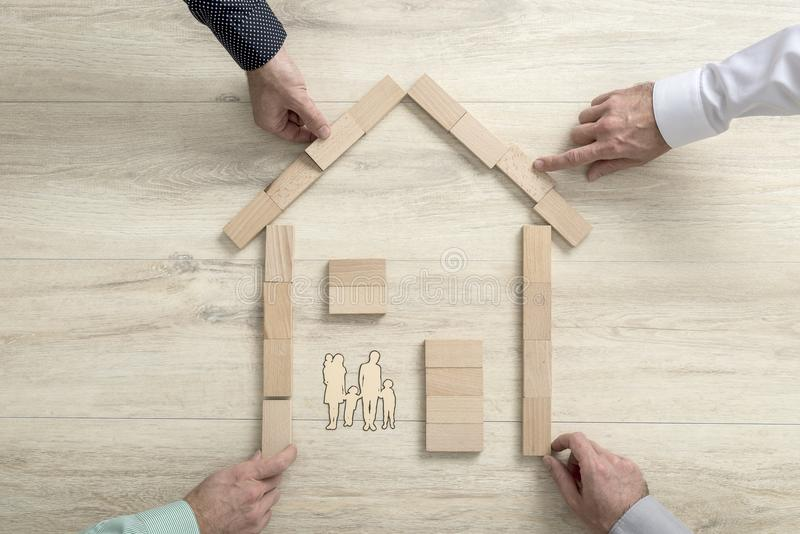 People making the shape of a residential house for a family stock photo