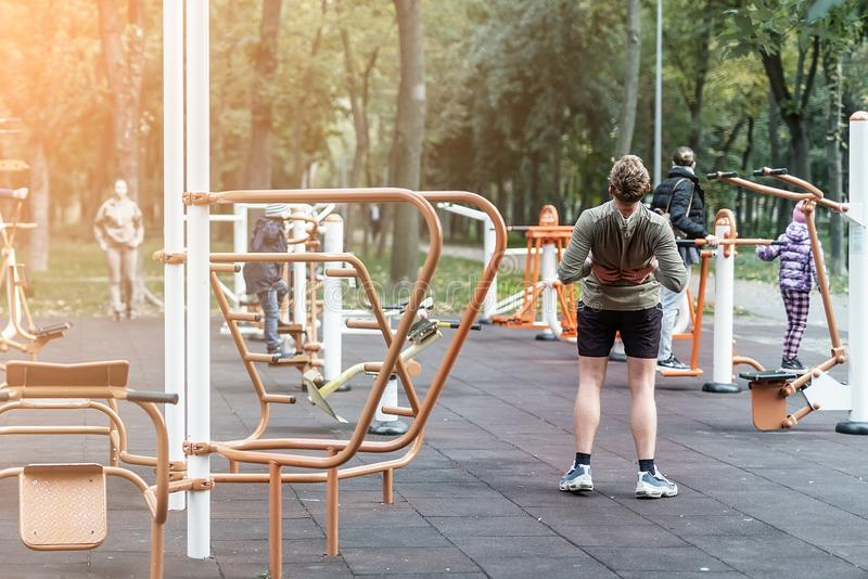 People making sport exercises and training at public outdoor gym area at city park. Healthy lifestyle concept stock images