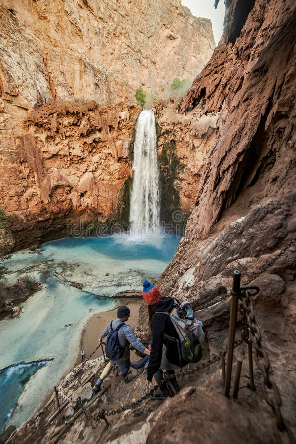 The decent down Mooney Falls, Supai, AZ. People making their way down the steep climb to the base of Mooney Falls in Havasupai royalty free stock images