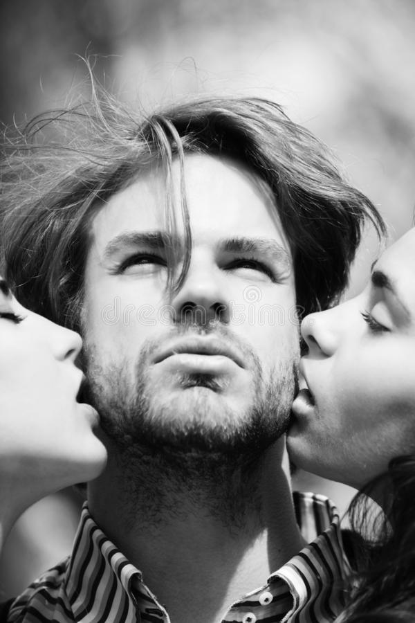 People, man getting kiss by two adorable girls royalty free stock images