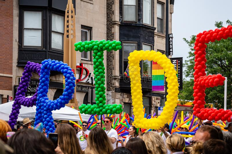 People marching with colorful balloons that spell the word `Pride`. Lakeview, Chicago-June 30, 2019: People marching with rainbow color balloons that spell the royalty free stock image