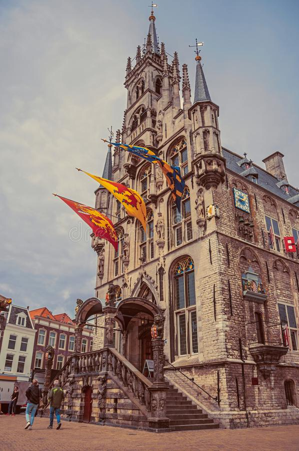People at Market Square with gothic City Hall and flags in cloudy day at Gouda. stock photo