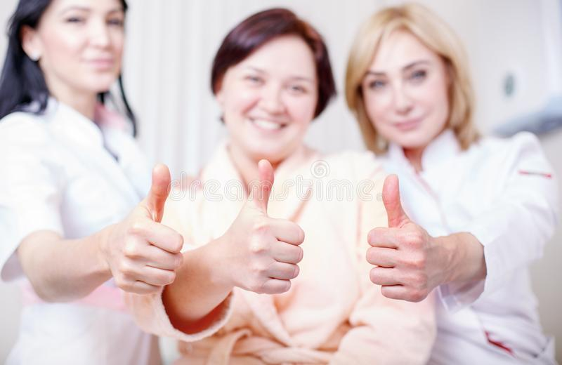 Doctors with a happy patient show like. People, medicine and health care concept - happy female doctors and patient at clinic office show thumbs up, show like stock photo