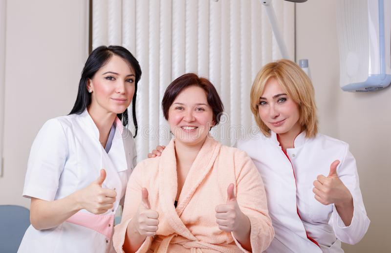 Doctors with a happy patient show like. People, medicine and health care concept - happy female doctors and patient at clinic office show thumbs up, show like stock image