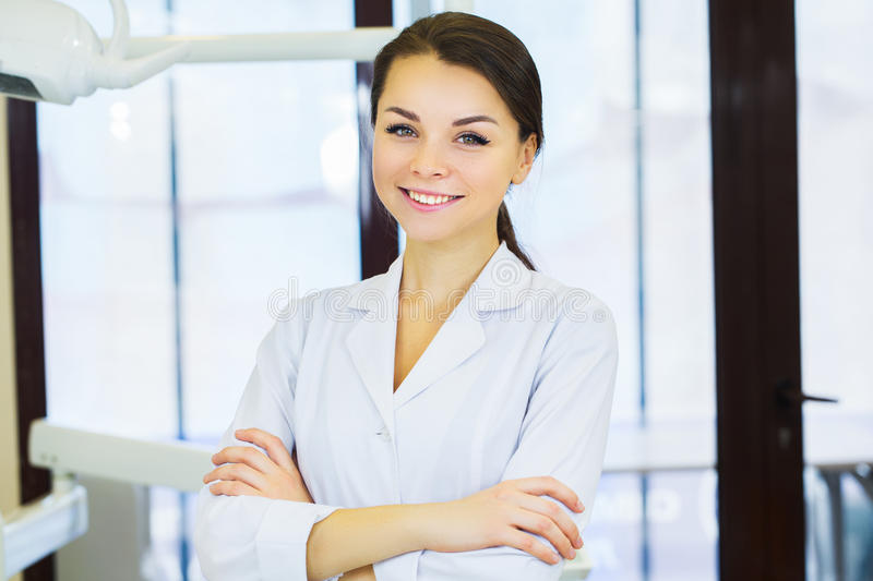 People, medicine, stomatology and healthcare concept - happy young female dentist with tools over medical office background royalty free stock photography