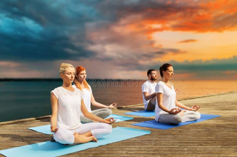 People meditating in yoga lotus pose outdoors stock photo