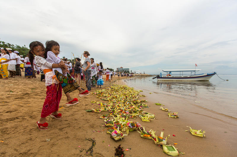 People during Melasti Ritual. SANUR, BALI - MAR 18, 2016: Unidentified people during Melasti Ritual. Ceremony is held on the edge of the beach with the aim to stock images