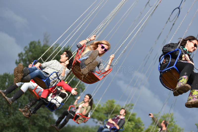 People in merry go round, swing ride, highland spinner stock images