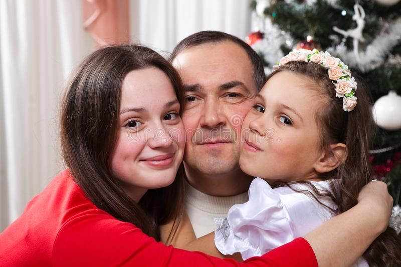 People, motherhood, family, christmas and adoption concept - happy father and daughter hugging at home. People, motherhood, family, christmas and adoption stock images