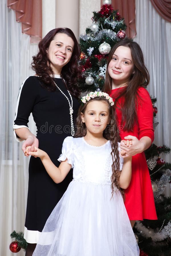 People, motherhood, family, christmas and adoption concept - happy mother and daughter hugging at home. People, motherhood, family, christmas and adoption royalty free stock image