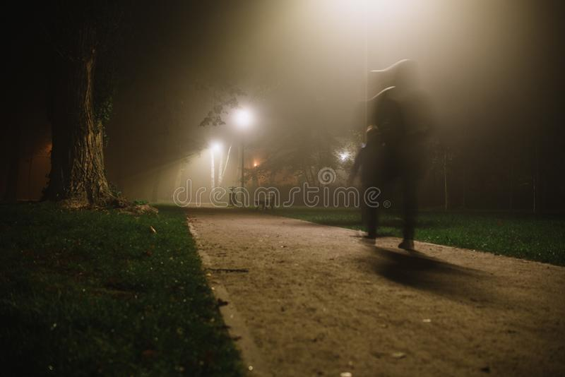 People motion blur in the park, night and heavy fog stock photos