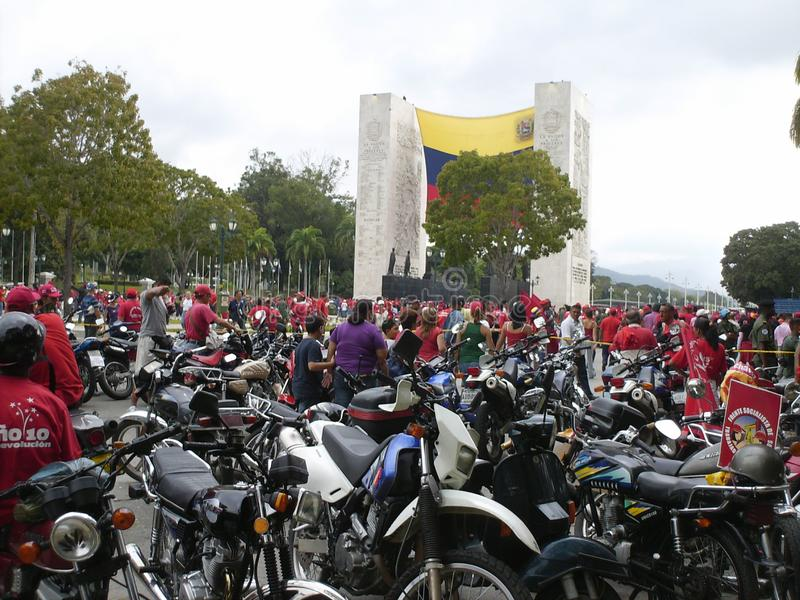 People and motorcycles in political demonstration in the capital of Venezuela, the city of Caracas, next to commemorative monument royalty free stock images