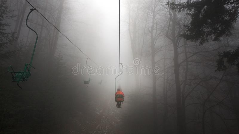 Ski lift in the fog. People on the Mountain lift in foggy weather royalty free stock photos