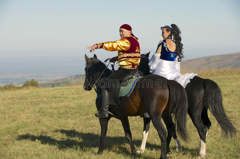 People in national dresses ride on horseback at countryside, circa Almaty, Kazakhstan. stock photography